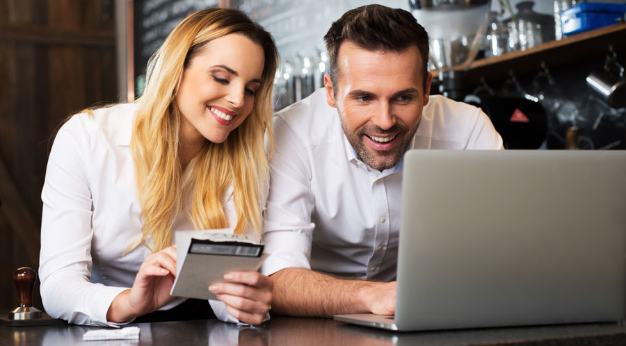 A smiling couple looks at a laptop enjoying Real Estate CRMs Software For Real Estate Agents